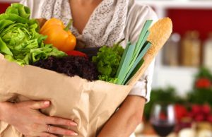 43218252 - young woman holding grocery shopping bag with vegetables standing in the kitchen.