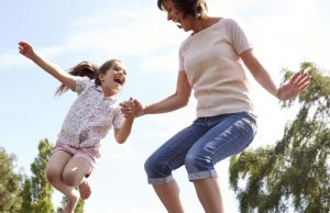 42309820 - mother and daughter bouncing on trampoline together