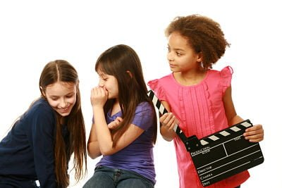 diverse-group-of-girls-with-one-whispering-and-other-holding-film-slate_opt
