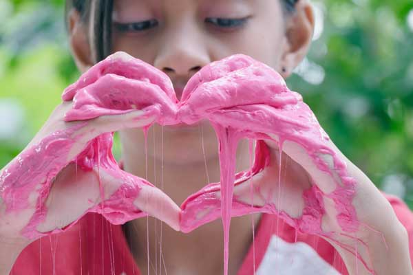 Young girl trying out home made slime