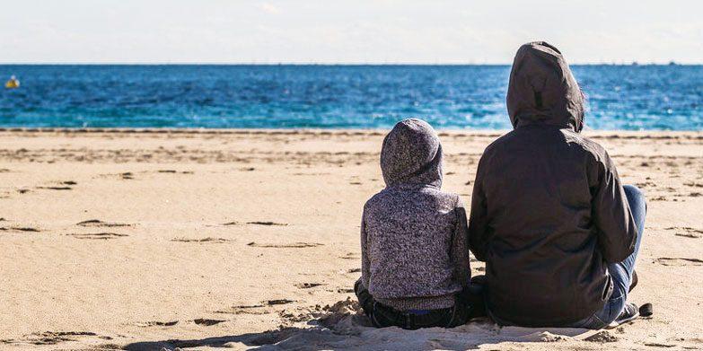 Sad mum and son on beach