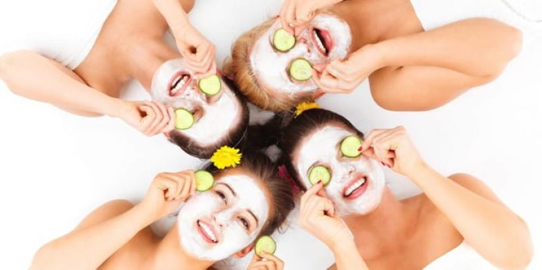 26741067 - a picture of four friends enjoying their time in spa with facial masks over white background